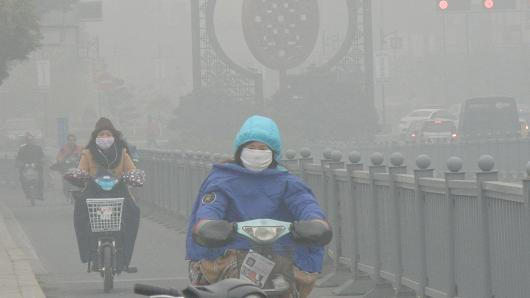 Cyclists wearing masks ride in heavy smog on December 7, 2015